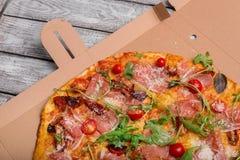 Plan rapproché d'une pizza dans une boîte de carton Pizza italienne traditionnelle sur un fond gris Nourritures nutritives La liv photos libres de droits