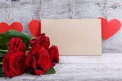 Plan rapproché d'une rose rouge, avec une enveloppe de papier, sur un fond des coeurs rouges, le concept des vacances Photographie stock
