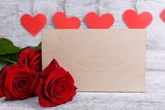 Plan rapproché d'une rose rouge, avec une enveloppe de papier, sur un fond des coeurs rouges, le concept des vacances Photos libres de droits