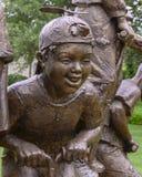 Plan rapproché d'une sculpture en bronze des enfants sur des bâtons de pogo par Gary Price à Dallas Arboretum et au jardin botani photos libres de droits