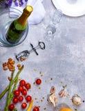Plan rapproché d'une table grise avec le plat, champagne, tomates, asperge, verres, tire-bouchon, fleurs sur un fond gris Photos libres de droits