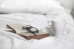 Plan rapproché d'une tasse de coffe, de vieux livre et de verres bordés sur un oreiller blanc. Photos stock