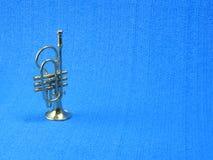 Plan rapproché d'une trompette miniature sur le fond bleu images libres de droits