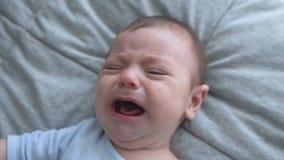 Plan rapproché de bébé nouveau-né pleurant Mensonges nouveau-nés étroits de visage, vue en gros plan et supérieure banque de vidéos