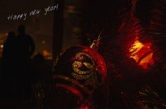 Plan rapproché de babiole rouge pendant d'un arbre de Noël décoré et des silhouettes de jeunes couples ou de jeune mariée étreign images libres de droits