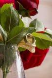 Plan rapproché de bague de fiançailles pendant d'une feuille du rouge r de floraison Photographie stock libre de droits