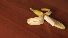 Plan rapproché de banane épluchée sur le fond en bois banque de vidéos