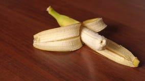 Plan rapproché de banane épluchée sur le fond en bois clips vidéos