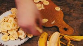 Plan rapproché de banane de coupe sur le conseil en bois avec le couteau banque de vidéos