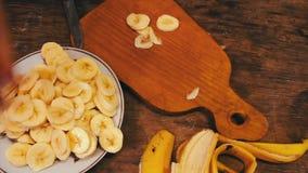 Plan rapproché de banane de coupe sur le conseil en bois avec le couteau clips vidéos