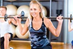 Plan rapproché de Barbell de levage Rod With Friends In Gym de jeune femme Image libre de droits