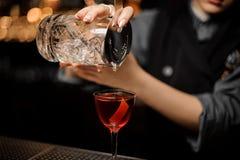 Plan rapproché de barman féminin faisant le cocktail d'alcool utilisant le tamis image libre de droits