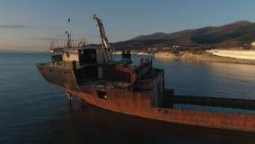 Plan rapproché de bateau rouillé abandonné à terre contre le beaux ciel, montagnes et littoral de coucher du soleil projectile Vi clips vidéos