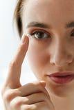 Plan rapproché de belle femme appliquant le cristallin dans l'oeil photographie stock libre de droits