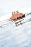 Plan rapproché de belle femme détendant dans la piscine Image libre de droits