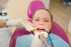 Plan rapproché de bouche d'ouverture de petite fille au loin pendant le traitement dentaire de la cavité buccale Image stock