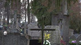 Plan rapproché de bougie et de croix sur les pierres graves et les personnes brouillées 4K banque de vidéos