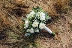 Plan rapproché de bouquet de mariage sur l'herbe Photos stock