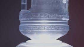 Plan rapproché de bouteille d'eau dans le refroidisseur sur le fond noir action L'eau la plus pure dans le refroidisseur avec des banque de vidéos