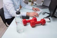 Plan rapproché de bouteille d'eau et d'haltère image libre de droits