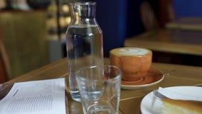 Plan rapproché de bouteille de l'eau et de tasse de café sur la table dans le café Art L'atmosphère confortable de la pause de mi image libre de droits