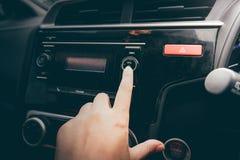 Plan rapproché de bouton de rotation de main du ` s de femmes de radio dans la voiture images stock