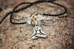 Plan rapproché de bracelet avec la fille de yoga en position de lotus photographie stock