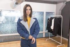 Plan rapproché de brune dans un magasin essayant sur une veste de denim avec un collier photos libres de droits