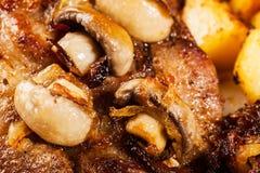 Plan rapproché de côtelette rôtie de porc avec des champignons image stock