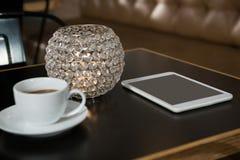 Plan rapproché de café, de comprimé numérique et de bougie allumée sur la table Photographie stock libre de droits