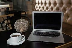 Plan rapproché de café, d'ordinateur portable et de bougie allumée sur la table Image libre de droits
