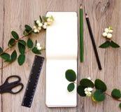 Plan rapproché de carnet et de papeterie sur le fond en bois Décoré des branches vertes de snowberry Vue supérieure, configuratio Photographie stock