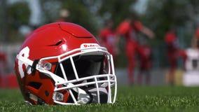 Plan rapproché de casque de football sur le fond des joueurs de football de malaxage banque de vidéos