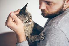 Plan rapproché de chat et d'homme Portrait d'un chat de Devon Rex et d'un jeune type de barbe images stock