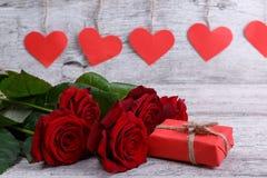 Plan rapproché de cinq roses rouges, avec l'emballage cadeau rouge, sur un fond des coeurs de papier, concept de vacances Photographie stock libre de droits