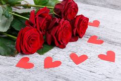 Plan rapproché de cinq roses rouges sur un fond gris avec chaotiquement d'étendre les coeurs de papier, le concept des vacances Images libres de droits