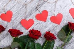 Plan rapproché de cinq roses rouges, sur un fond gris avec une guirlande des coeurs de papier, le concept des vacances Image libre de droits