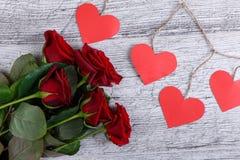 Plan rapproché de cinq roses rouges, sur un fond gris avec une guirlande des coeurs de papier, le concept des vacances Photo libre de droits