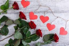 Plan rapproché de cinq roses rouges, sur un fond gris avec une guirlande des coeurs de papier, le concept des vacances Photos stock