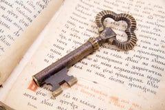 Plan rapproché de clé placé sur la bible de livre de cru Photo stock