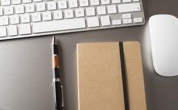 Plan rapproché de clavier, de souris, et de stylo avec un carnet Photos stock