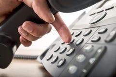 Plan rapproché de composer un numéro de téléphone sur un teleph noir de ligne terrestre images stock