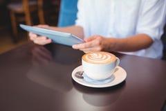 Plan rapproché de comprimé numérique et de café sur la table Photos libres de droits