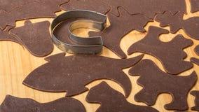 Plan rapproché de couper des pains d'épice de Noël sur le panneau de pâtisserie image stock