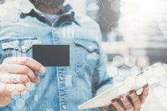 Plan rapproché de crédit vide noir, affaires, appelant, carte de visite et comprimé numérique à disposition de jeune homme d'affa images stock