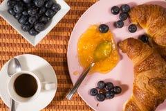 Plan rapproché de croissant, de myrtilles, de café et de confiture au-dessus d'un tablecl Image libre de droits