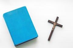 Plan rapproché de croix chrétienne en bois et bible sur le fond blanc Photographie stock libre de droits