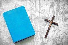 Plan rapproché de croix chrétienne en bois et bible sur le fond blanc Photos stock