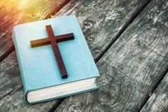 Plan rapproché de croix chrétienne en bois sur la bible, la bougie brûlante et les perles de prière sur la vieille table photos stock