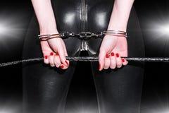 Plan rapproché de cul de femme dans la combinaison-pantalon de latex Image stock